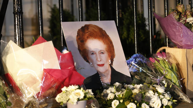 """Flowers placed by well-wishers surround a portrait of former British Prime Minister Margaret Thatcher outside her home in Belgravia, London, Monday, April 8, 2013. Margaret Thatcher, the combative """"Iron Lady"""" who infuriated European allies, found a fellow believer in Ronald Reagan and transformed her country by a ruthless dedication to free markets in 11 bruising years as prime minister, died Monday. She was 87 years old. (AP Photo/Sang Tan)"""