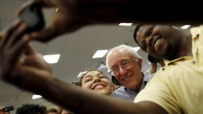 Vermont Senator and U.S. Democratic presidential candidate Sanders snaps a selfie with supporters at a campaign town hall in Manchester