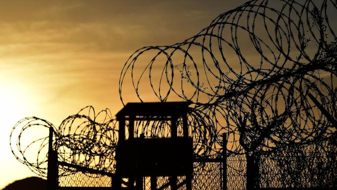 """Photo taken on April 09, 2014 and reviewed by the US military shows the razor wire-topped fence and a watch tower at the abandoned """"Camp X-Ray"""" detention facility at the US Naval Station in Guantanamo Bay, Cuba during an escorted visit"""