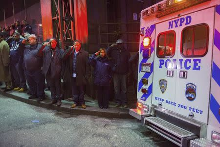 Police officers salute as vehicles containing the bodies of two New York Police officers who were shot dead drive by in the Brooklyn borough of New York