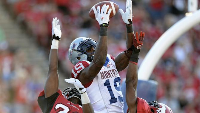 Montreal Alouettes' Green goes high for the ball but cannot make the catch against Calgary Stampeders' Wall and Bell during the second half of their CFL football game in Calgary