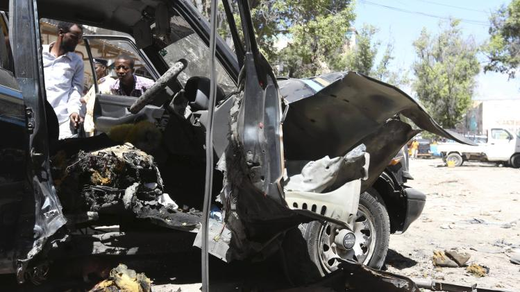 Residents look at the remains of the car of Somali lawmaker Isaak Mohamed Rinoco, who was killed by a bomb planted in his car by Islamist militants, in the Hamaerweyne District of Somalia' capital Mogadishu