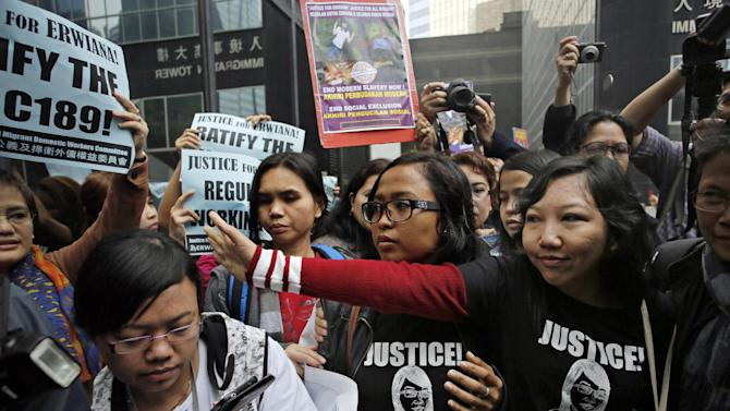Indonesian maid Erwiana Sulistyaningsih, front right, waves to supporters as she arrives at a court in Hong Kong, Friday, Feb. 27, 2015.  A Hong Kong court sentenced a mother of two to six years in prison on Friday for abusing her Indonesian maid in a case that triggered outrage over its brutality. Law Wan-tung was found guilty earlier this month on 18 charges, including assault, grievous bodily harm, criminal intimidation and failure to pay wages or give time off work to Sulistyaningsih. (AP Photo/Vincent Yu)