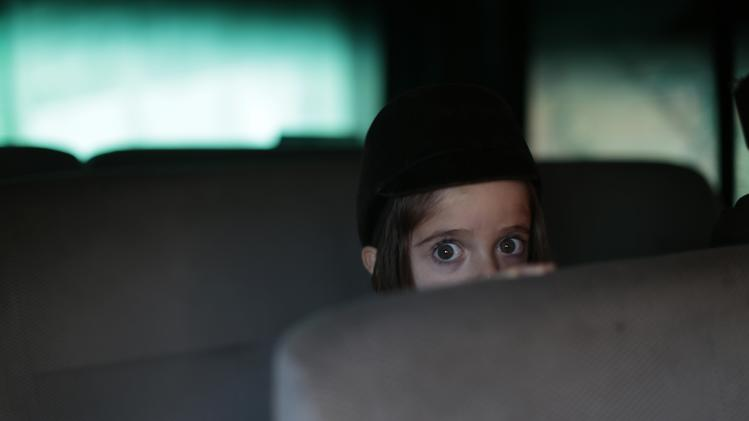 A young member of a Jewish community peeks from behind a seat while sitting on a van in the village of San Juan La Laguna