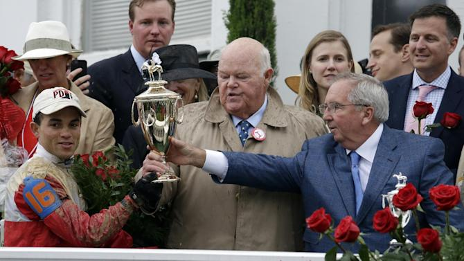 Orb jockey Joel Rosario, left, trainer Claude McGaughey, right, and owner Ogden Phipps celebrate after winning the 139th Kentucky Derby at Churchill Downs Saturday, May 4, 2013, in Louisville, Ky. (AP Photo/J. David Ake)