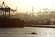 File picture shows a barge navigating past cranes and freight ships at the port of Hamburg. The German trade surplus grew in June, as imports declined faster than exports, official data showed on Wednesday