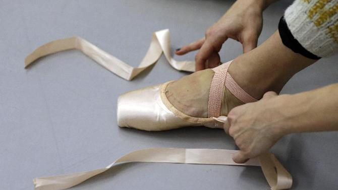 In this Wednesday, Feb. 27, 2013 photo, a Pennsylvania Ballet dancer laces up her shoe during a class at the ballet's new facility in Philadelphia. The company is celebrating its 50th birthday with a new facility and a season of performing brand new works and classic pieces. (AP Photo/Matt Rourke)