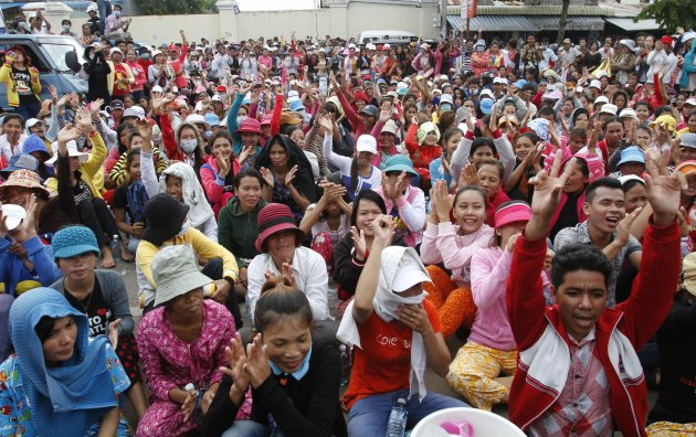 Garment factory workers block a street during a protest in Phnom Penh