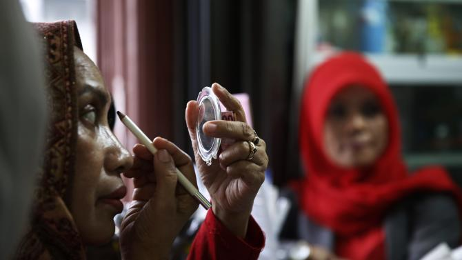 A woman applies eyebrow pencil make-up before buying it at Pasar Atjeh in Banda Aceh