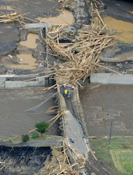 Riverbanks are covered with mud and woods carried by floodwater in Takeda, Kumamoto Prefecture, Japan, Thursday, July 12, 2012. Heavy rains hit southern Japan, triggering flashfloods, mudslides and destroying dozens of homes. (AP Photo/Kyodo News) JAPAN OUT, MANDATORY CREDIT, NO LICENSING IN JAPAN, CHINA, HONG KONG, SOUTH KOREA AND FRANCE