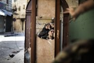 "<p>Free Syrian Army fighters are reflected in a mirror they use to see a Syrian Army post only 50 meters away as they man a position in the Old City of Aleppo. Serious human rights violations have soared dramatically in Syria, a top UN investigator said Monday, calling for ""appropriate action"" against perpetrators of atrocities in the wartorn country.</p>"