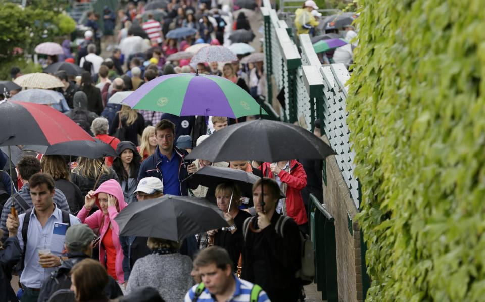 Spectators shelter under umbrellas at the All England Lawn Tennis Championships in Wimbledon, London, Thursday, June 27, 2013. (AP Photo/Alastair Grant)