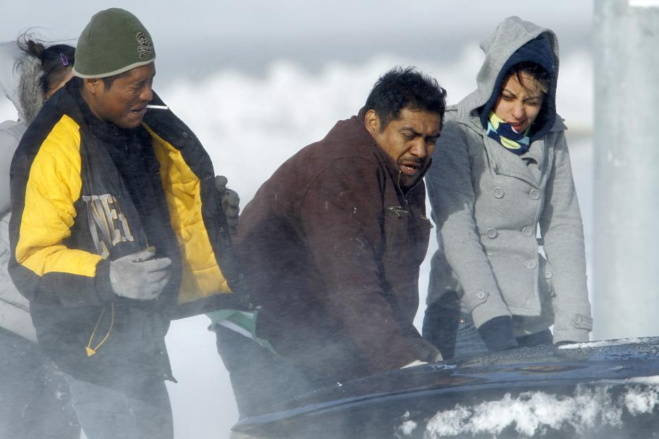 People react to a strong gust of wind as they try to free a car from deep snow in Philadelphia, Monday, Dec. 27, 2010. (AP Photo/Matt Rourke)