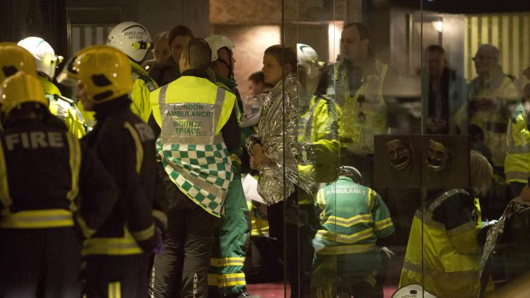 People receive medical attention after part of the ceiling at the Apollo Theatre on Shaftesbury Avenue collapsed in central London