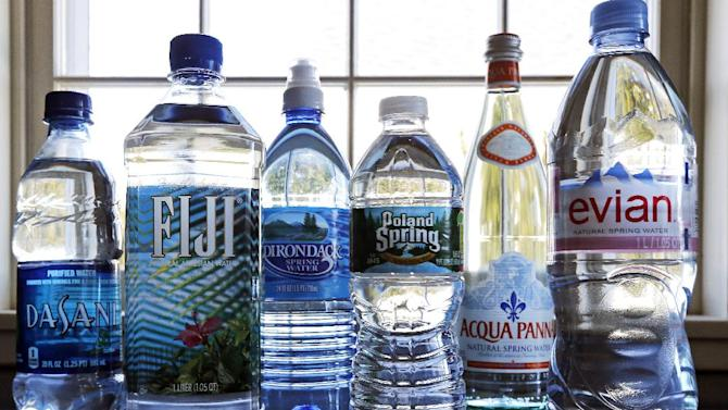 In this Tuesday, March 5, 2013 photo, a selection of bottled waters stands on a kitchen counter in East Derry, N.H. Soda's reign as America's most popular drink could be entering its twilight years, with plain old bottled water making a run for the top spot. Already, bottled water has surged past juice, milk and beer in terms of per capita consumption. The result is that bottled water is slowly closing the gap for the No. 1 spot. (AP Photo/Charles Krupa)
