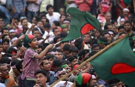A boy waves a Bangladesh national flag as he chants a slogan before a mass funeral as the body of Rajib Haider, an architect and blogger who was a key figure in organising demonstrations, arrives at Shahbagh intersection in Dhaka February 16, 2013. More than 100,000 Bangladeshi protesters, angered by the killing of one of their leaders, poured back onto the streets of the capital on Saturday to demand the death penalty for those found guilty of war crimes in the 1971 independence conflict. REUTERS/Andrew Biraj