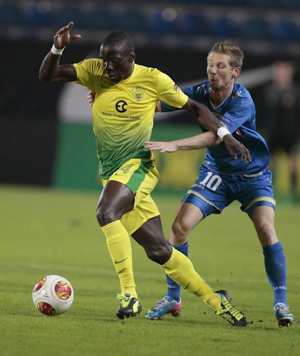 Anzhi's Benoit Angbwa, left, runs away from Tromso's Thomas Drage as they struggle for the ball during the Europa League group K soccer match between Anzhi Makhachkala and Tromso IL at Saturn stadium