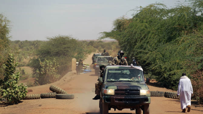 Malian soldiers patrol the entrance of Gao, northern Mali, Friday Feb. 8, 2013, where a suicide bomber on a motorcycle killed himself attempting to blow up an army checkpoint. It was the first known time a suicide bomber has operated in Mali. (AP Photo/Jerome Delay)