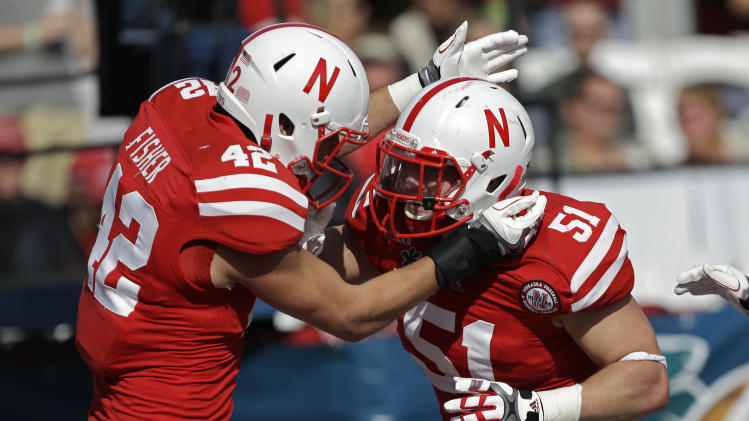 Nebraska linebacker Sean Fisher (42) congratulates teammate linebacker Will Compton (51) after Compton intercepted a Georgia pass for a touchdown during the first half of the Capital One Bowl NCAA football game, Tuesday, Jan. 1, 2013, in Orlando, Fla. (AP Photo/John Raoux)