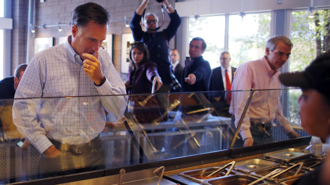 Republican presidential candidate and former Massachusetts Governor Mitt Romney and U.S. Senator Rob Portman (R-OH) (R) order food at a Chipotle Restaurant in Denver