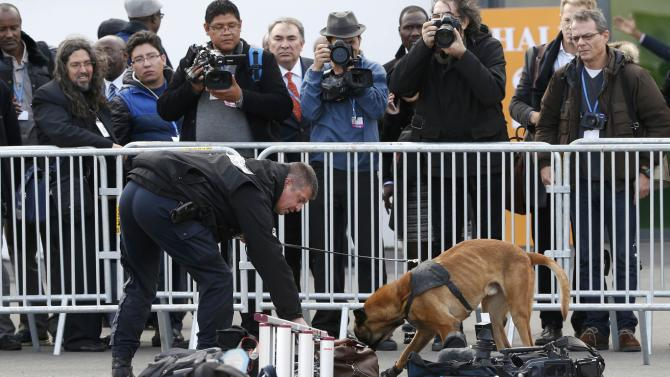 A French policeman with a sniffer dog inspects journalists equipment on the opening day of the World Climate Change Conference 2015 at Le Bourget, near Paris