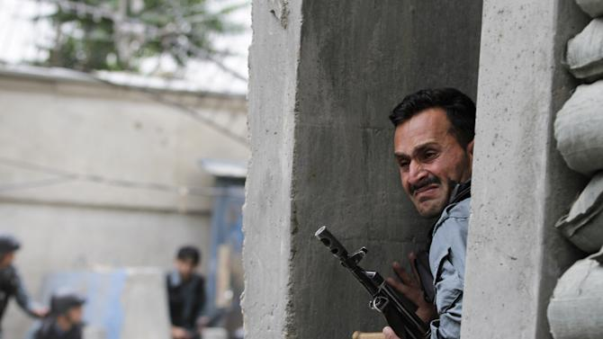 An Afghan policeman takes cover following a suicide attack in Kabul, Afghanistan, Friday, May 24, 2013. A suicide bomber struck in the heart of the Afghan capital on Friday, sending a plume of smoke billowing over Kabul and setting up a gun battle in the second major attack in the city in little over a week, police said. (AP Photo/Ahmad Jamshid)