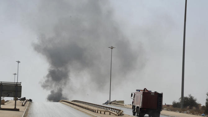 A fire truck drives towards smoke caused by an attack by Islamist militias during clashes with forces led by renegade Libyan Gen. Khalifa Hifter in Benghazi, Libya, Wednesday, Oct. 15, 2014. Islamist militias fought Wednesday with forces loyal to Hifter, who vows to seize the eastern city of Benghazi, as a top militia commander accused Egypt of bombing his positions with warplanes. (AP Photo/Mohammed el-Sheikhy)