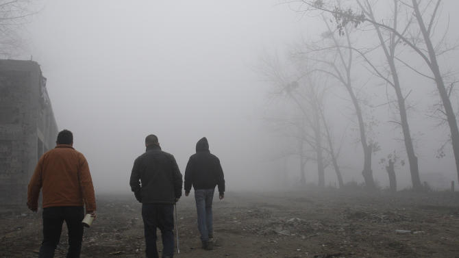 Bosnian animal activists and dog catchers walk on a foggy morning searching for stray dogs in the Sarajevo suburb Dobrnja, Bosnia, on Tuesday, Nov. 27, 2012. Bosnia passed a law nearly four years ago banning the killing of strays, alarmed at a sharp rise in canine slaughter as wild dogs proliferated on Bosnian streets. But people ignored the law, largely because authorities failed to provide alternatives such as sterilization. Sarajevo has become the only city in Bosnia where the law is respected _ thanks to a new city-funded dog shelter run by animal protection activist Amela Turalic that performs sterilizations. (AP Photo/Amel Emric)