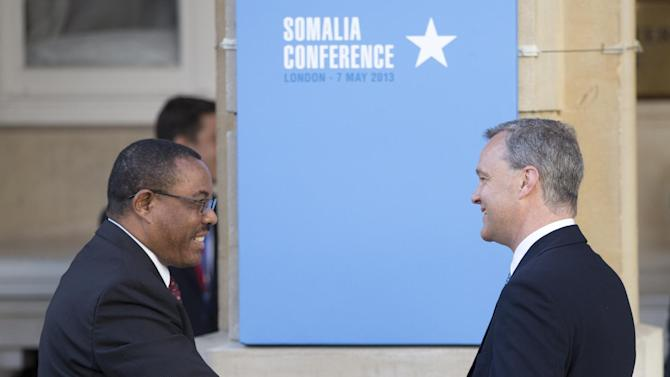 Prime Minister of Ethiopia Hailemariam Desalegn, left, is greeted as he arrives for the Somalia Conference held at Lancaster House in London, Tuesday May 7, 2013. British Prime Minister David Cameron is welcoming Somalia's president and a host of international leaders to London for a conference aimed at securing support for the government in Mogadishu after two decades of conflict. Man at right is unidentified. (AP Photo/Alastair Grant)
