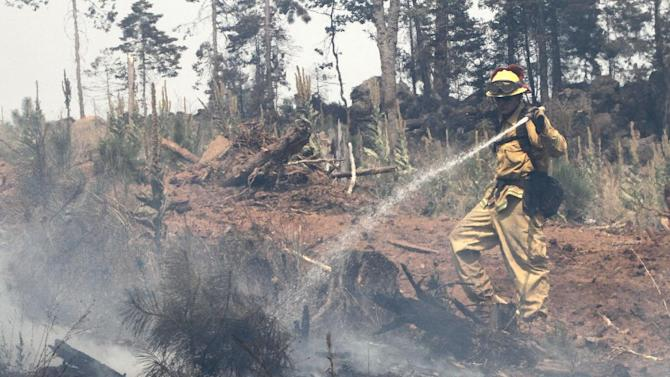 Firefighter Chuck Mitchell hoses down a hot spot of the Ponderosa Fire near Viola, Calif., Monday, Aug. 20, 2012.   More than 1,400 fire fighters are battling the fire that has destroyed seven homes, burned 23 square miles.  The fire that started Saturday is just 5 percent contained. (AP Photo/Rich Pedroncelli)