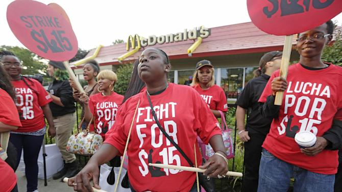 FILE - In this Sept. 14, 2014 file photo,  protesters participate in a rally outside a McDonald's on Chicago's south side as labor organizers escalate their campaign raise the minimum wage for employees to $15 an hour.   As Democrats across the country make an election-year push to raise the minimum wage, they are also looking to motivate younger people, minorities and others in their base to go to the polls on Nov. 4th. The party has put questions on the ballot in five states asking voters whether the minimum wage should be increased. (AP Photo/M. Spencer Green, File)