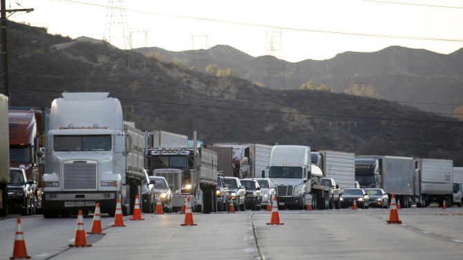 Trucks backed up along Interstate 5 north of Los Angeles on Friday, Jan. 11, 2013. The California Highway Patrol has partially reopened a 40-mile stretch of Interstate 5 north of Los Angeles that was closed for many hours due to snow. The CHP began escorting southbound motorists through the high mountain pass Friday morning. Northbound lanes are still closed. (AP Photo/Nick Ut)