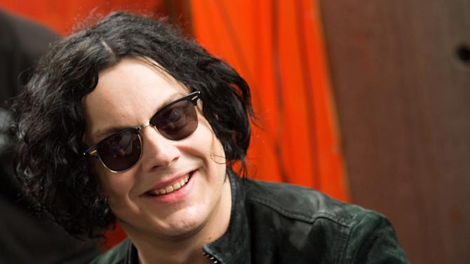 """FILE - In this June 24, 2011 file photo, Jack White signs copies of the record he made with Stephen Colbert in New York. White will kick off the release of his first solo album with a concert streamed live online, to be directed by Gary Oldman. The show will be the first installment of American Express' """"Unstaged"""" series, which pairs top musical acts with renown filmmakers. White's concert at New York's Webster Hall will be streamed live April 27, 2012, at 9 p.m. EST on VEVO.  (AP Photo/Charles Sykes, File)"""