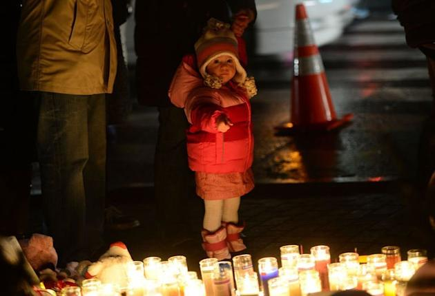 A child points at candles at a  shrine to the victims of the Newtown school shooting, Connecticut, December 16, 2012
