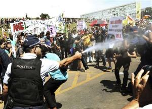 A policeman sprays anti-government demonstrators with tear gas outside the Congress in Brasilia