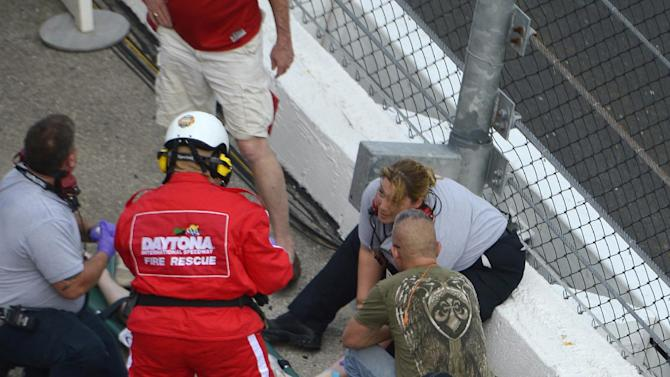 Emergency personnel attend to injured spectators in front of the grandstands after Kyle Larson's car hit the safety wall and fence along the front stretch on the final lap of the NASCAR Nationwide Series auto race at Daytona International Speedway in Daytona Beach, Fla., Saturday, Feb. 23, 2013. (AP Photo/Phelan M. Ebenhack)