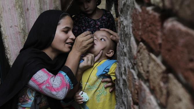 A Pakistani health worker gives polio vaccine to a child at a neighborhood of Lahore, Pakistan, Monday, May 4, 2015.  Pakistan's beleaguered battle to eradicate polio is threatening a global, multi-billion dollar campaign to wipe out the disease worldwide. (AP Photo/K.M. Chaudary)