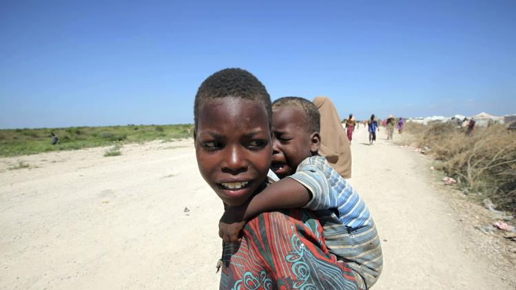 A displaced Somali girl plays with her sibling along a dusty road in Jowhar