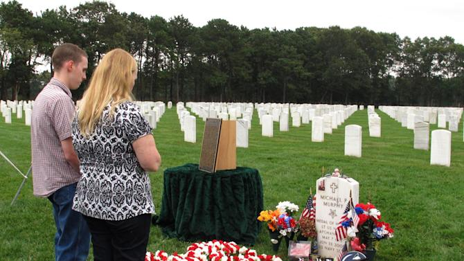 In this Oct. 2, 2012 photo, John Murphy and his mother, Maureen Murphy pray at the gravesite of their brother and son, Navy SEAL Lt. Michael Murphy following a memorial service at Calverton National Cemetery in Calverton, N.Y. The memorial service was attended by crew from the USS Michael Murphy, a Navy destroyer named for the Medal of Honor recipient killed in Afghanistan in 2005.   (AP Photo/Frank Eltman)