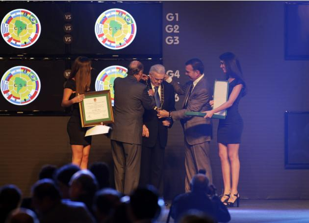 President of the Brazilian Football Confederation Jose Maria Marin receives an award in honor of his career from the CONMEBOL during the draw for the 2014 Copa Libertadores in Luque