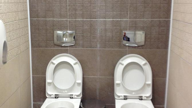 ALTERNATIVE CROP TO LON110 This photo taken on Friday Jan. 17, 2014, shows two toilets at the cross-country skiing and biathlon center for next monthÌs Olympics in Sochi, Russia. Although two toilets and only one stall like this are not common in Russia, social media users have responded by posting other pictures of toilets standing side by side. One said this was standard at Russian soccer stadiums. (AP Photo/Steve Rosenberg, BBC)