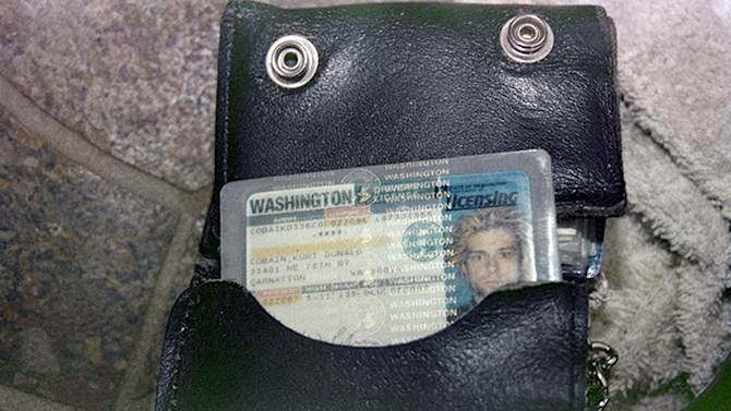 """FILE - This April 1994 photo from the Seattle Police Department shows a wallet containing Kurt Cobain's Washington state driver's license, found at the scene of his suicide, in Seattle. A handwritten note police discovered in Kurt Cobain's wallet after his suicide disparages his wife Courtney Love. CBS News reports Wednesday, April 30, 2014, that the note was taken from Cobain's wallet when police arrived at his home on April 8, 1994, after Cobain fatally shot himself. The note was never made public. CBS obtained it from the Seattle Police via a public information request. The network reports that the undated note, apparently written by Cobain on stationery from San Francisco's Phoenix Hotel, is written like a mock wedding vow. It references Love as Cobain's """"lawful shredded wife"""" who would be """"siphoning"""" his money for drugs. (AP Photo/Seattle Police Department)"""