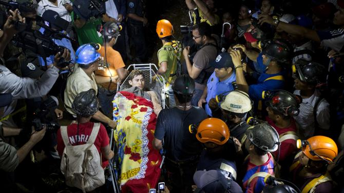 A rescue miner is carried away on a stretcher as he is evacuated from the El Comal gold and silver mine in Bonanza, Nicaragua, Friday, Aug. 29, 2014. The first 11 of 24 freelance gold miners trapped by a collapse in this mine have been rescued and crews were working early Saturday to free more, officials said. (AP Photo/Esteban Felix)