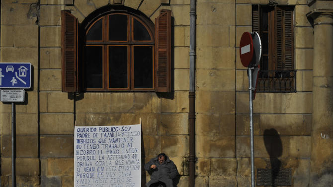 A man sits on one street beside to a banner reading, ''Dear audience. I am a parent and I have to keep three children. I have no job and I have no unemployment benefits. I'm here because necessity compels me. I hope you're never in this situation because it is very hard and sad but I have to fight for my children. Please help me. Thank you'', in Pamplona northern Spain on Friday, Jan. 25, 2013. (AP Photo/Alvaro Barrientos)
