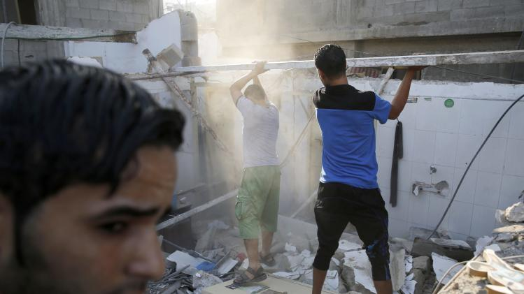 Palestinians salvage material from a destroyed home in Gaza City