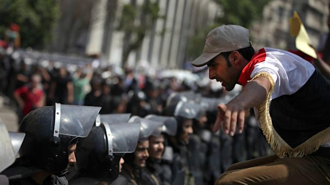 A supporter of Egypt's ousted President Mohammed Morsi, talks to riot police standing guard during a demonstration near Tahrir Square in downtown Cairo, Egypt, Wednesday, July 17, 2013. Several hundred supporters of Egypt's deposed president massed outside the Cabinet building Wednesday in Cairo, expanding their protests denouncing the country's new government and demanding the reinstatement of Islamist leader Mohammed Morsi.(AP Photo/Khalil Hamra)