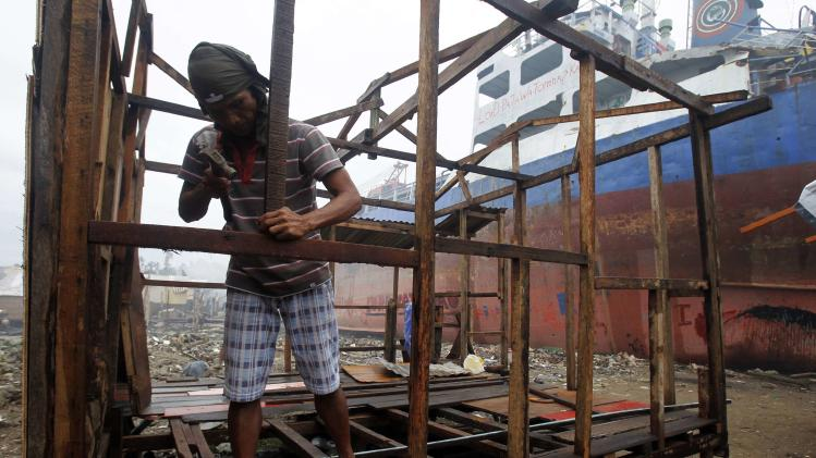 Renato Delijon, married with two kids, reconstructs his shanty after it was devastated by a cargo ship that was washed ashore by super typhoon Haiyan in Tacloban city