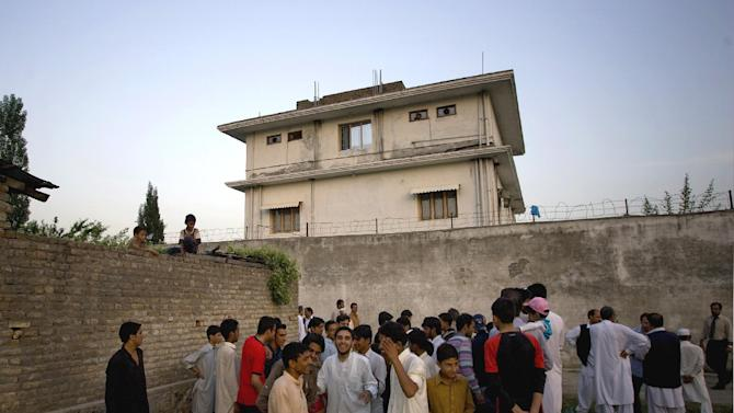 "In this May 3, 2011 file photo, local residents gather outside a house, where al-Qaida leader Osama bin Laden was caught and killed in Abbottabad, Pakistan. After U.S. Navy SEALs killed Osama bin laden in Pakistan in May 2011, top CIA officials secretly told lawmakers that information gleaned from brutal interrogations played a key role in what was one of the spy agency's greatest successes. CIA director Leon Panetta repeated that assertion in public, and it found its way into a critically acclaimed movie about the operation, Zero Dark Thirty, which depicts a detainee offering up the identity of bin Laden's courier, Abu Ahmad al- Kuwaiti, after being tortured at a CIA ""black site."" As it turned out, Bin Laden was living in al Kuwaiti's walled family compound, so tracking the courier was the key to finding the al-Qaida leader.    (AP Photo/B.K.Bangash,File)"