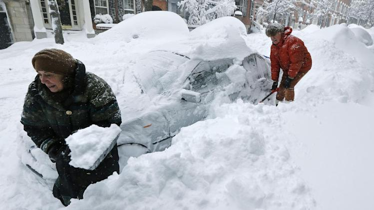 Deb Hanley, left, and Frank McGuire dig about three feet of snow from around their car outside their home in the Beacon Hill neighborhood of Boston, Saturday, Feb. 9, 2013. The Boston area received about two feet of snow from a winter storm. A howling storm across the Northeast left the New York-to-Boston corridor shrouded in 1 to 3 feet of snow Saturday, stranding motorists on highways overnight and piling up drifts so high that some homeowners couldn't get their doors open. More than 650,000 homes and businesses were left without electricity. (AP Photo/Charles Krupa)