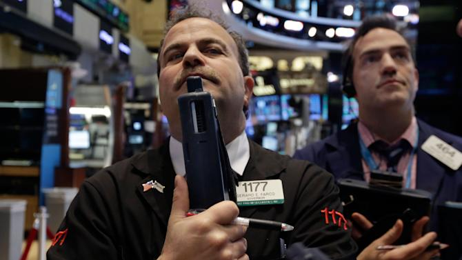Traders Gerard Farco, left, and Gregory Rowe work on the floor of the New York Stock Exchange Tuesday, Jan. 27, 2015. U.S. stocks are tumbling in midday trading, weighed down by disappointing forecasts from big-name companies and an unexpected drop in orders of long-lasting goods. (AP Photo/Richard Drew)